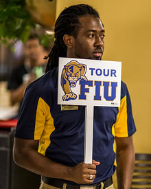 Student holding FIU campus tour sign