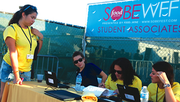 Students checking in at the student associates table at the Food Network South Beach Food and Wine Festival presented by Food and Wine
