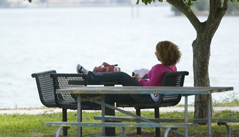 Student lounging on a picnic table next to Biscayne Bay