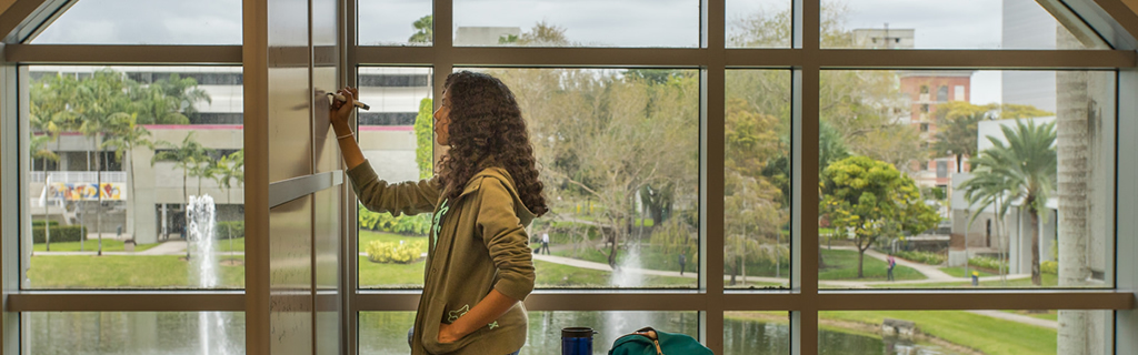 Female student writing on a whiteboard with a large window in the background